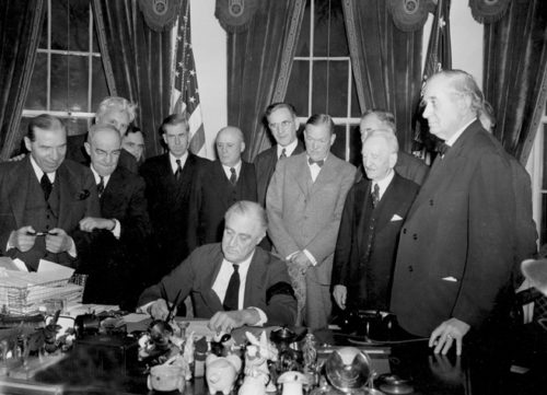 U.S. President Franklin D. Roosevelt signs the declaration of war following the Japanese bombing of Pearl Harbor, Dec. 7, at the White House in Washington, D.C., Dec. 8, 1941 at 3:08 p.m. EST. Watching from left to right are, Rep. Sol Bloom, D-N.Y.; Rep. Luther Johnson, D-Texas; Rep. Charles A. Eaton, R-N.J.; Rep. Joseph Martin, R-Mass.; Vice President Henry A. Wallace; House Speaker Sam Rayburn, D-Texas; Rep. John McCormack, D-Mass.; Sen. Charles L. McNary, R-Ore.; Sen. Alben W. Barkley, D-Ky.; Sen. Carter Glass, D-Va.; and Sen. Tom Connally, D-Texas. (AP Photo)